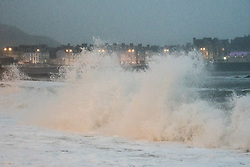 © Licenced to London News Pictures. Aberystwyth Wales UK, Tuesday 18 September 2018. UK Weather: As the day breaks, the strong winds of ex-hurricane Helene bring waves crashing into the seafront in Aberystwyth on the Cardigan Bay coast of West Wales. Winds are lower than originally forecast, with maximum speeds of around 40mph , gusting up to 50mph in exposed places . photo © Keith Morris / LNP