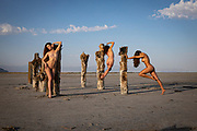 Three nude women posing with old pier pilings in the Great Salt Lake, Utah