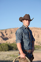 handsome cowboy holding a lasso on a ranch