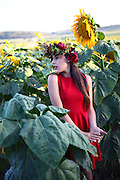 Preteen with wreath in a field of sunflowers