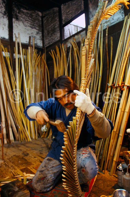 Chibata Kanjuro, whose family has been making bows since the 15th century, bends the bamboo frame of a new bow in his workshop in Kyoto, Japan..