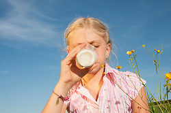 Girl (10-11) drinking glass of milk, eyes closed, portrait, close-up