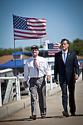 Republican presidential candidate Mitt Romney walks with USS Yorktown Director Mac Burdette (L) during a visit to the USS Yorktown museum on October 6, 2011 in Charleston, South Carolina. Romney addressed a group of veterans and called for increased military spending to maintain national security.