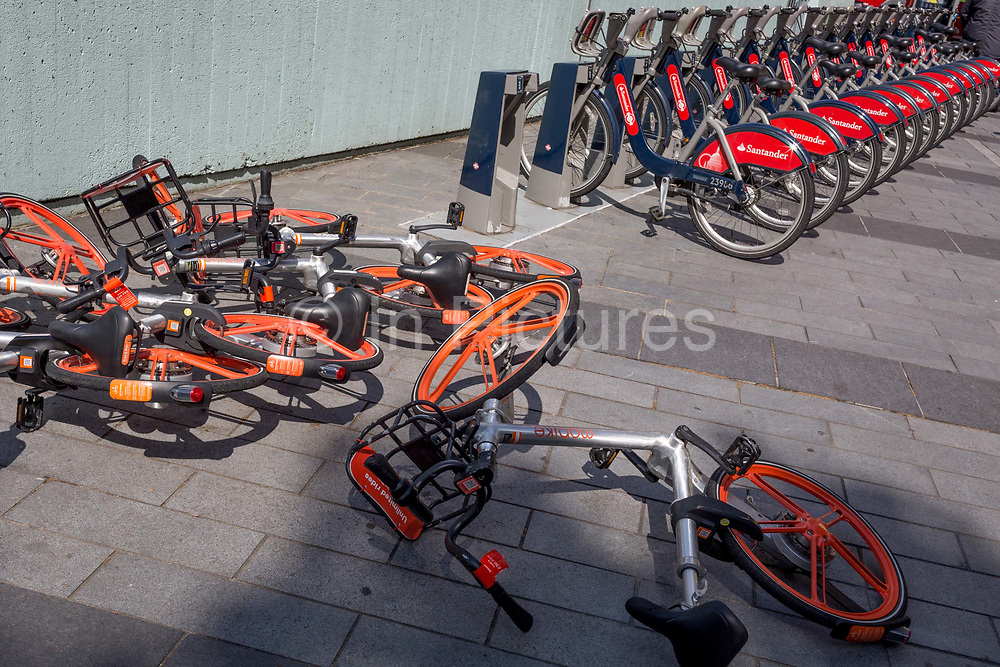 A pile of collapsed Mobikes lie on the ground next to docked Santander rental bikes at Waterloo, on 15th August 2019, in London, England.