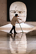 A cleaning woman sweeps around a colossal Olmec stone head at the Museum of Anthropology in the historic center of Xalapa, Veracruz, Mexico. The Olmec civilization was the earliest known major Mesoamerican civilizations dating roughly from 1500 BCE to about 400 BCE.