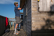 Ensuring that all doors and locks are secured, a visitor locks a beach hut on the seaside promenade, on 18th July 2020, in Whitstable, Kent, England.
