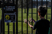 Dissappointed users pass or stop at the gates as Brockwell Park is closed after overcrownding yesterday - A sunny day and people are out in reasonable numbers, in SW London, to get their daily exercise. But in these areas the fears of the police dont seem to have been realised as teh numbers are less than yesterday. The 'lockdown' continues for the Coronavirus (Covid 19) outbreak in London.