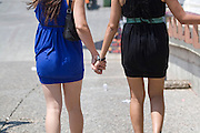 Two young teen girls walk hand in hand
