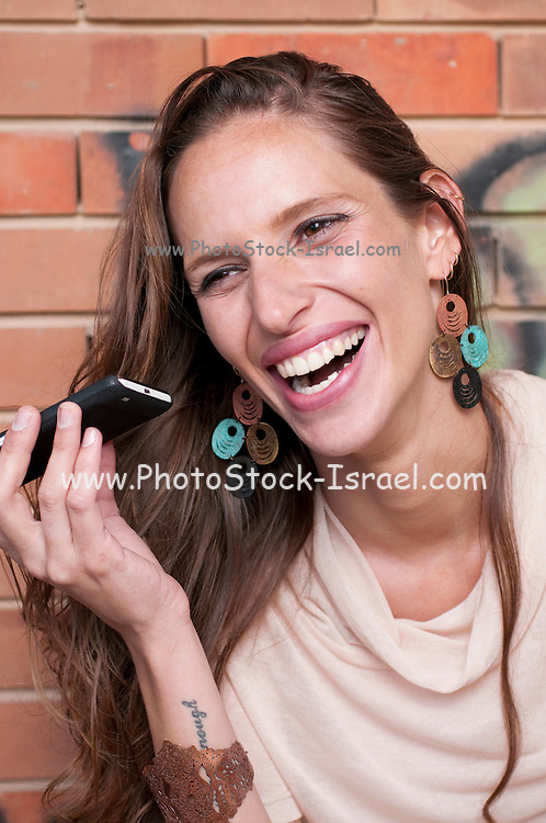 A hip and trendy young woman talks on her mobile phone in front of a brick wall with graffiti Model release available