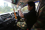 August 2012: A new breed of modern Kelabit native with his four-wheel drive. Balak, Janing's son, uses the vehicle for hunting. He can make enough money selling jungle meat, and transporting passengers to pay off the $800 a month loan. Limbang district, Sarawak, Borneo<br /> <br /> The sound of chainsaws is not too distant, oil palm plantations are looming and the pipeline is right next door. Long Adang and Long Gita, Limbang Sarawak, Borneo..The huge Petronas Sabah-Sarawak pipeline is being built across the Borneo rainforest through native areas. Petronas is the government cash cow which funds about 45% of its budget. New roads are being built, though much of the transport follows the existing roads and infrastructure created by logging. Whilst the government heralds the project as a source of jobs for local people, it is unlikely to bring much but wanton damage to rainforest habitat and paving the way for further deforestation by oil palm plantations. Sarawak's primary rainforests have been systematically logged over decades, threatening the sustainable lifestyle of its indigenous peoples who relied on nomadic hunter-gathering and rotational slash & burn cultivation of small areas of forest to survive. Now only a few areas of pristine rainforest remain; for the Dayaks and Penan this spells disaster, a rapidly disappearing way of life, forced re-settlement, many becoming wage-slaves. Large and medium size tree trunks have been sawn down and dragged out by bulldozers, leaving destruction in their midst, and for the most part a primary rainforest ecosystem beyond repair. Nowadays palm oil plantations and hydro-electric dam projects cover hundreds of thousands of hectares of what was the world's oldest rainforest ecosystem which had some of the highest rates of flora and fauna endemism, species found there and nowhere else on Earth, and this deforestation has done irreparable ecological da