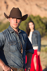 girl walking towards a handsome cowboy outdoors