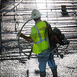 An xxperienced concrete worker uses a vibrating tool during an early morning concretepour with smoothing and shaping on the top floors of a high-rise parking garage in downtown Austin on Augut 22, 2020. Major construction projects continue unabated during the coronavirus shutdowns in Texas.