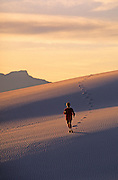 Image of a woman running on the dunes at White Sands National Monument in New Mexico, American Southwest, model released by Randy Wells