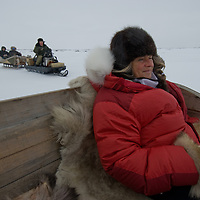 North of the Arctic Circle in Russia, Gretel Ehrlich rides in a sled behind a snowmobile, en route to a camp of the last remaining nomadic Komi reindeer herders.