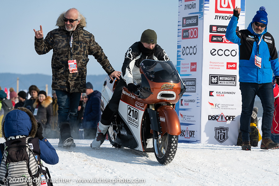 Team mechanic-tuner Simon Pitelet on custom bike builder Bertrand Dubet's partially streamlined Aprilia RSV4 racer as the team gets introduced for the grand entry with Bertrand on the left and Fred Billion to the right during the Baikal Mile Ice Speed Festival. Maksimiha, Siberia, Russia. Saturday, February 29, 2020. Photography ©2020 Michael Lichter.