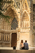 Couple sitting by Cathedral of Notre-Dame in Reims, France