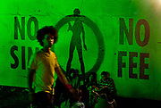 "Man lit by green light walking past ""No Sin, No Fee"" poster in the Alleys, Shangri-La. Glastonbury Festival 2010"