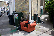 A dumped armchair and other domestic rubbish, fly-tipped on a street corner in south London. Abandoned on the pavement, the items have made a mess in this urban location. Furniture and household possessions have been added, perhaps by others, making this area look and feel intimidating. increase in amount of rubbish illegally dumped on roadsides and back alleys cost local authorities £45m in 2014. The figures also reveal the rising cost to the public purse of cleaning up and prosecuting people who dump rubbish, with the clearance bill for local authorities rising 24% to £45.2m.