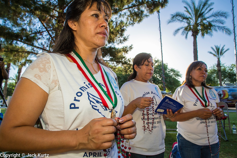 25 JUNE 2012 - PHOENIX, AZ:  25 JUNE 2012 - PHOENIX, AZ:  Immigration activists pray at the Arizona State Capitol in Phoenix, AZ, Monday before the US Supreme Court ruled on Arizona's immigration law, SB1070. The lawsuit, US v. Arizona, determines whether or not Arizona's tough anti-immigration law, popularly known as SB1070 is constitutional. Among other things, the law requires police officers to check the immigration status of anyone whom they arrest, allows police to stop and arrest anyone whom they believe to be an illegal immigrant, makes it a crime for someone to be in the state without valid immigration papers, and makes it a crime to apply for or hold a job in Arizona without proper papers. The federal government sued Arizona because it believes the law is invalid because it is trumped by federal immigration laws. The court struck down most of the law but left one section standing, the section authorizing local police agencies to check the immigration status of people they come into contact with.   PHOTO BY JACK KURTZ  PHOTO BY JACK KURTZ
