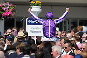 A winning jockey and horse are taken into the winners enclosure during Epsom Derby day in southern England.