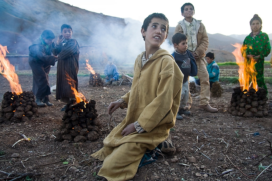 Children stand besides fire pits in the Berber town of Amezri in the M'Goun Massif, Central High Atlas, Morocco on November 4, 2007. Once the coals are hot, the children throw potatoes to roast in the fire and smash down the clay to trap the heat.