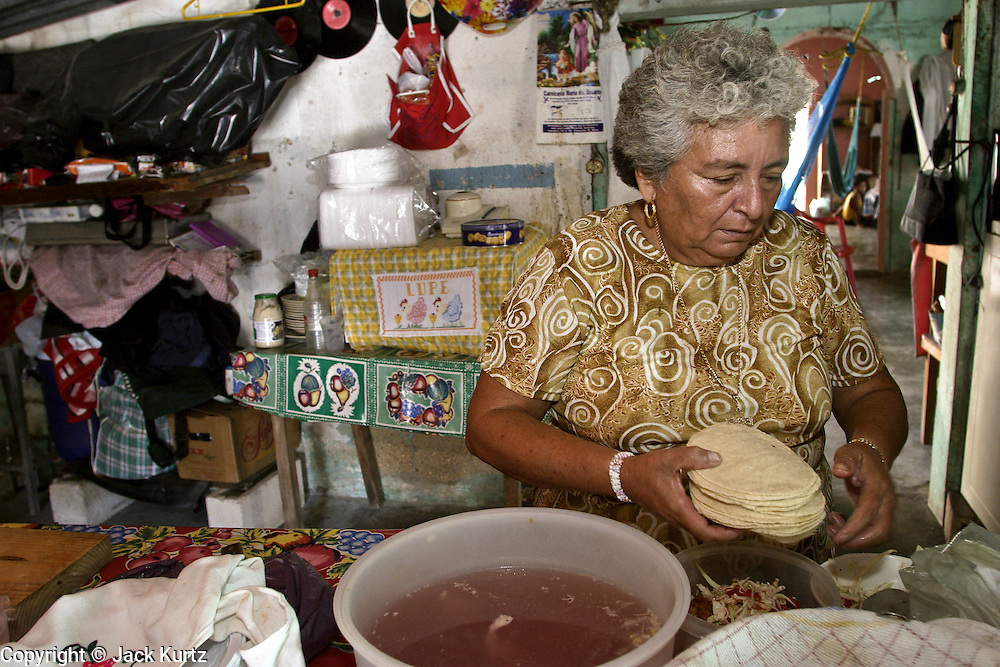 09 SEPTEMBER 2003 - CANCUN, QUINTANA ROO, MEXICO: Guadalupe Pacheco Medino prepares a take out dinner of chicken and tortillas for a customer in the Medino home in Cancun, Quintana Roo, Mexico, Sept 9, 2003. Medino supplement her family's income by preparing takeout meals for her neighbors. Her husband is a retired fisherman who also worked in the tourist industry before he was forced to retire for health reasons. Her sons still fish from open boats in the waters off Cancun. The family has lived in the region for years, since before Cancun was Cancun and was a small fishing community called Puerto Juarez. PHOTO BY JACK KURTZ  economy  labour  food  women  poverty  culture