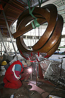 Oasis of the Seas at the shipyard in Turku, Finland where she is being built..Photos show Royal Caribbean's latest  ship 2 months before completion. ..A Welder attaching a brass statue in the Solarium.