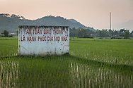 """Sign promoting road safety sits in a rice paddy near the town of Nghia Lo: """"Safety on the road means happiness for evey family,"""" Yen Bai Province, Northern Vietnam, Southeast Asia"""