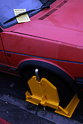 A wheel clamped car on a street in London, UK