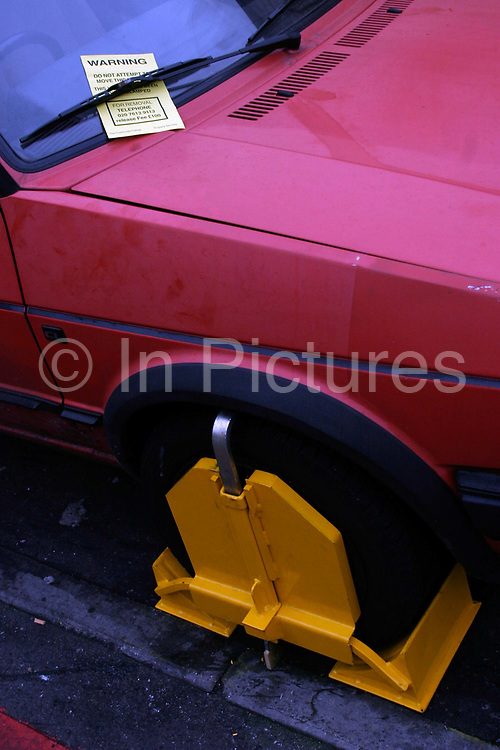 A wheel clamped car on a street in London, UK