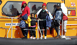 © Licensed to London News Pictures. 22/09/2021. Dungeness, UK. A young girl stands with a group of mostly African migrants at Dungeness in Kent as they are rescued by the RNLI as they crossed the English Channel. Hundreds of migrants have made the crossing in the calm weather this week. Photo credit: Sean Aidan/LNP