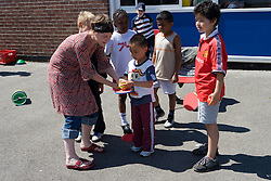 Group of children preparing to take part in sports day competition in school playground,