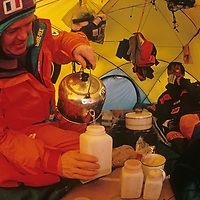 Will Steger fills water bottles with melted snow while Qin Dahe sips tea in their tent at the South Pole, about halfway through the 1989-1990 Trans-Antarctica Expedition.