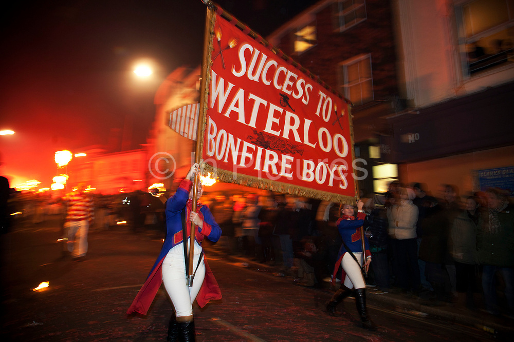 Lewes, UK. Monday 5th November 2012. Members of Waterloo bonfire society carry a banner on Bonfire Night celebration in the town of Lewes, East Sussex, UK which form the largest and most famous Guy Fawkes Night festivities. Held on 5 November, the event not only marks the date of the uncovering of the Gunpowder Treason and Plot in 1605, but also commemorates the memory of the 17 Protestant martyrs from the town burnt at the stake for their faith during the Marian Persecutions of 1555–57. There are six bonfire societies putting on parades involving some 3,000 people.