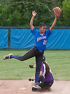 Middletown, New York - A Warwick baserunner slides into second base as the Middletown shortstop jumps for the ball during a varsity girls' softball game on May 27, 2014.
