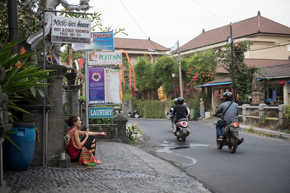 Bali, Indonesia - September 19, 2017: A young foreign woman, a yoga mat on her back, sits outdoors during a conversation on her smart phone in Ubud, Bali.