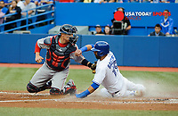 Jul 23, 2014; Toronto, Ontario, CAN; Blue Jays first baseman Jose Bautista (19) slides into home plate past Red Sox catcher Felix Doubront (22) to score in first innings at Rogers Centre. Mandatory Credit: Peter Llewellyn-USA TODAY Sports