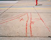 Member of the Red Arrows, Britain's RAF aerobatic team with airfield markings during airshow weekend.