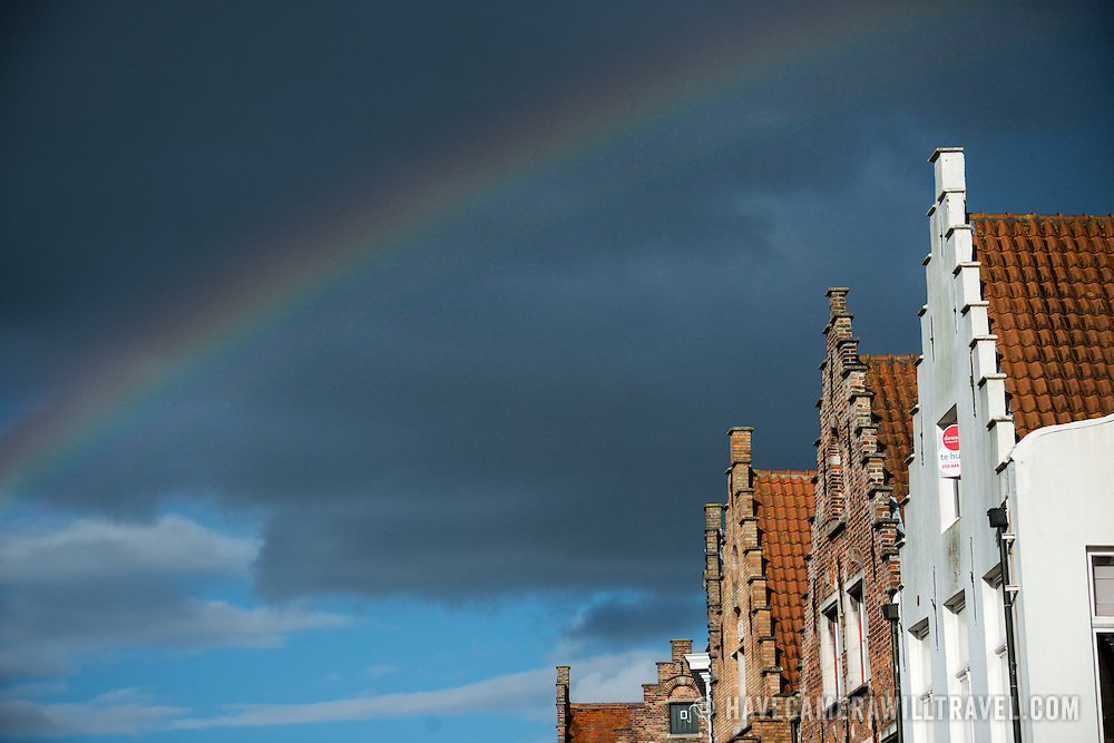 A rainbox stands out against dark clouds, arching over some of the historic architecture of Bruges, Belgium.
