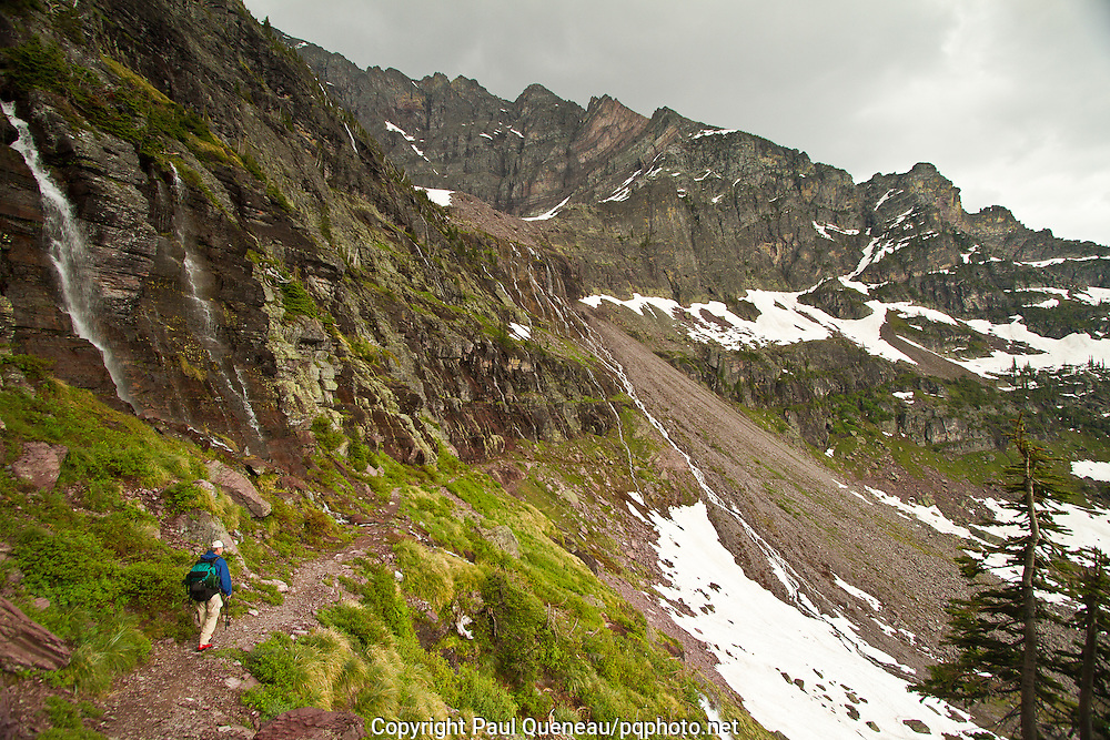 A backpacker traverses Glacier Basin near Sperry Chalet in Montana's Glacier National Park as the many fingers of Feather Woman Falls usher a long winter's snowfall to McDonald Lake thousands of feet below.