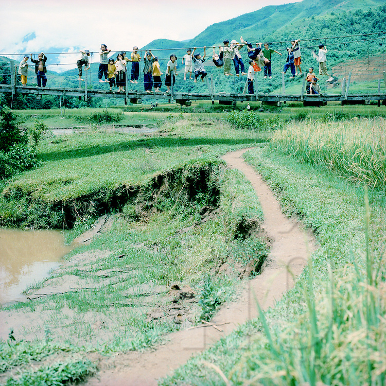 Hmong kids playing with the ropes of a bridge in the area of Sapa