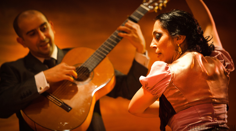Flamenco performers (male guitarist and female dancer) on stage in Almeria, Spain.