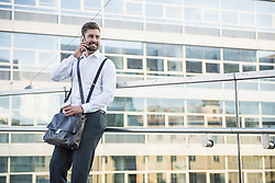 Businessman leaning against railing and talking on mobile phone, Munich, Bavaria, Germany