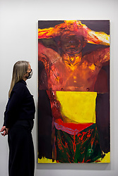 """© Licensed to London News Pictures. 03/12/2020. LONDON, UK. A staff member poses with """"Transfiguration (He's No Saint)"""", 2017.  Preview of """"Jennifer Packer: The Eye Is Not Satisfied With Seeing"""" at the Serpentine Gallery.  It is the American artist's first exhibition in a European institution and includes paintings and drawings from the past decade alongside recent works.  The exhibition opens to the public on 5 December. Photo credit: Stephen Chung/LNP"""