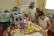 (MODEL RELEASED IMAGE). Breakfast during the children's summer vacation at the Brown family home in Riverview, Australia (outside of Brisbane) is low-key and unstructured. Everyone eats when the mood strikes them. Vanessa bustles about, scrambling eggs for Sinead and herself. The boys help themselves to cereal and sandwiches. Meanwhile, Doug cooks himself a hearty breakfast of fried meat, onions, gravy, and buttered toast, and oversees his wife's meal of cereal and juice; since her stroke, Marge has been trying to eat a more healthy diet. Hungry Planet: What the World Eats (p. 29).