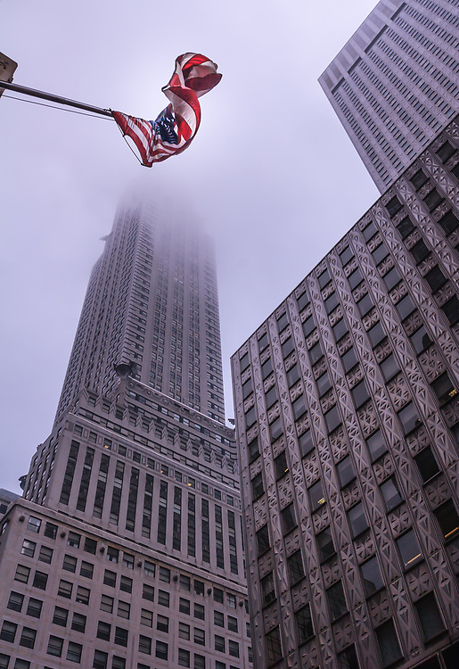 The United States flag and The Chrysler Building in New York, USA. The Chrysler Building is a classic example of Art Deco architecture and considered by many contemporary architects to be one of the finest buildings in New York City.