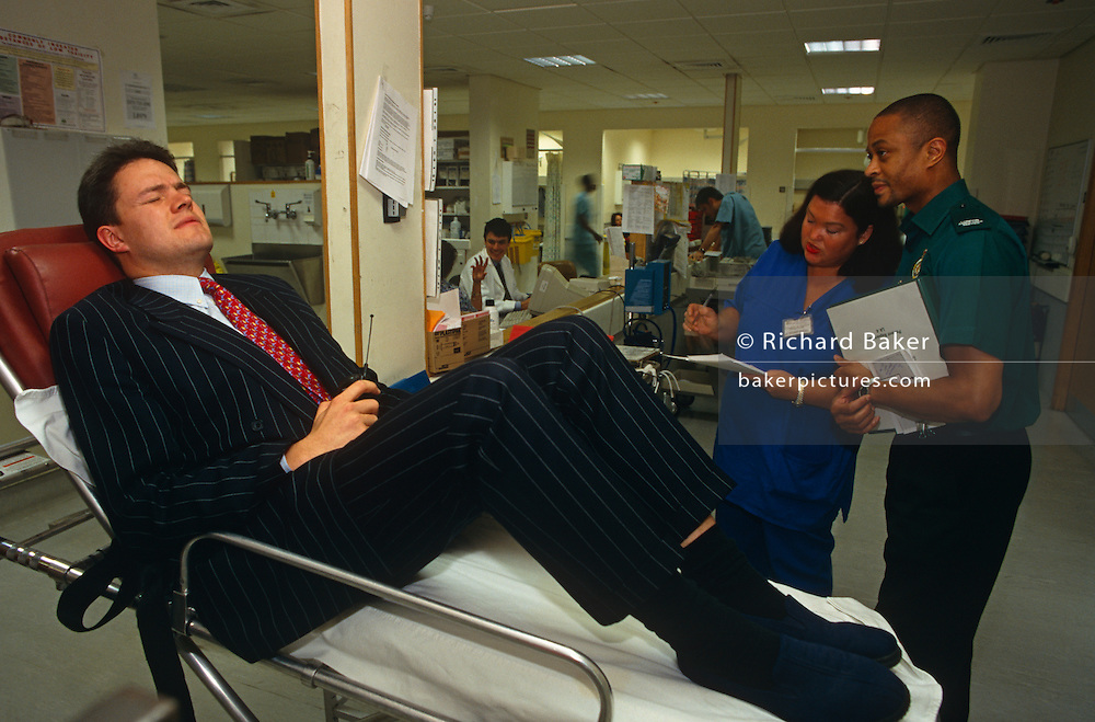 """On a busy Friday night in the Accident and Emergency section of the royal London Hospital, Whitechapel, East London, a city businessman, still in his pin-stripe suit, with his mobile phone and wearing slippers, sits rigid, grimacing in pain on with severe back pain a trolley (gurney) while two medical staff using a clipboard assess his treatment. The Royal London is one of London's oldest hospitals, having been founded in 1740 and is a major teaching hospital in Whitechapel, East London. It is part of the Barts and the London NHS Trust, alongside St Bartholomew's Hospital (""""Barts""""), which is a couple of miles away."""