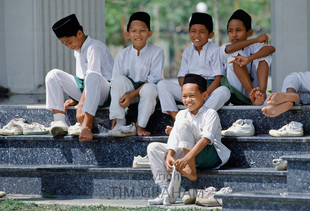 Young boys putting shoes and socks back on after visiting Shah Alam muslim mosque in Kuala Lumpur, Malaysia