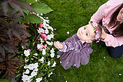 Baby girl with mom touching flowers in Boston Public Gardens