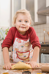Girl kneading dough for cookies, smiling, portrait